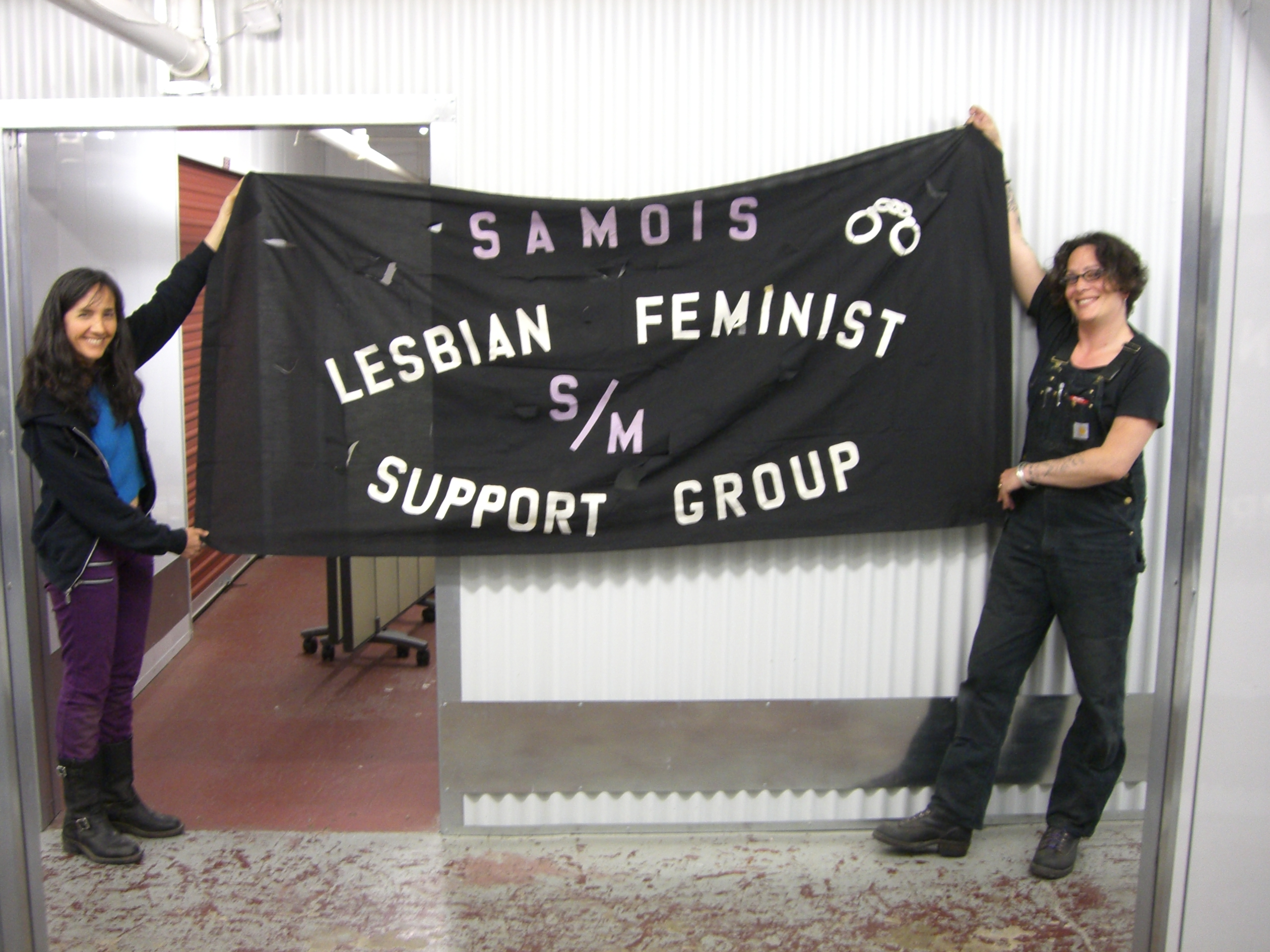 "Marlene Hoeber and Dorian Katz holding a parade banner that reads ""SAMOIS lesbian feminist s/m support group"""