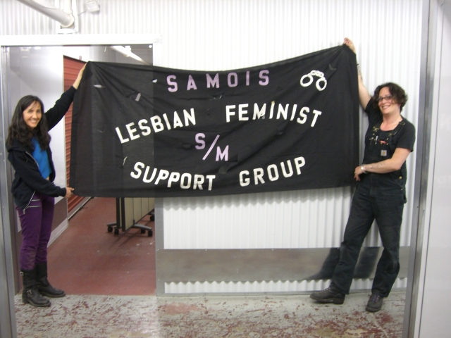 "Marlene Hoeber and Dorian Katz holding a parade banner that reads ""SAMOIS lesbian feminist s/m support group"""